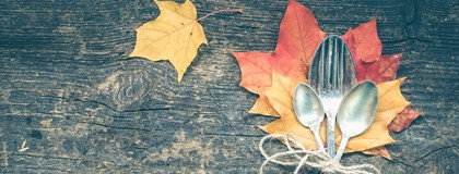 Fork, knife and spoon on wooden table with fall leaves.