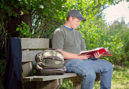 Student sitting outdoors on bench while reading